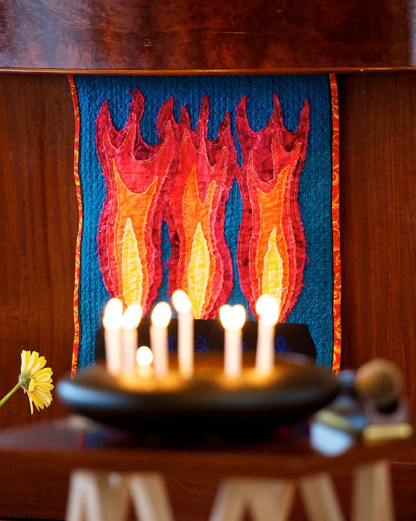 A tray of candles placed in front of a quilt displaying candles