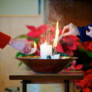 Image of two hands lighting candles seated in a decorative bowl